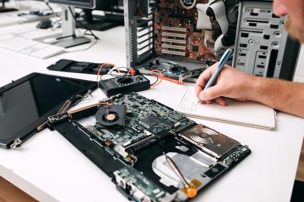 Computer-motherboard-diagnose, nahaufnahme. programmierer prüft den schaltkreis und notiert die ergebnisse auf papier. elektronisches reparatur-, reparatur-, renovierungskonzept Premium Fotos