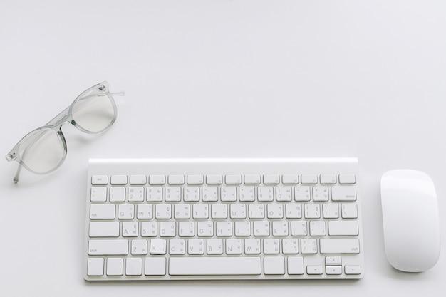 Computer-tastatur und maus mit brille auf weißem hintergrund Premium Fotos