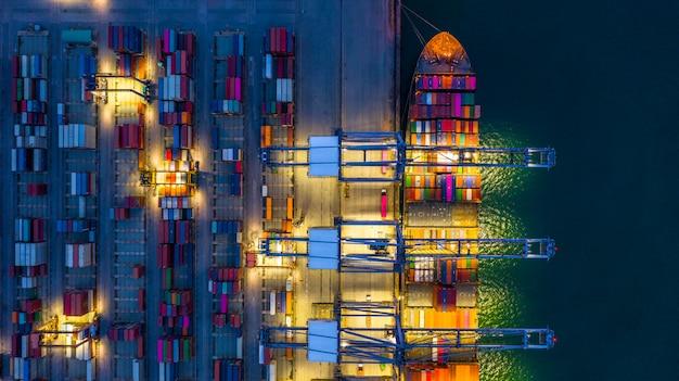 Containerschiff, das nachts arbeitet. Premium Fotos
