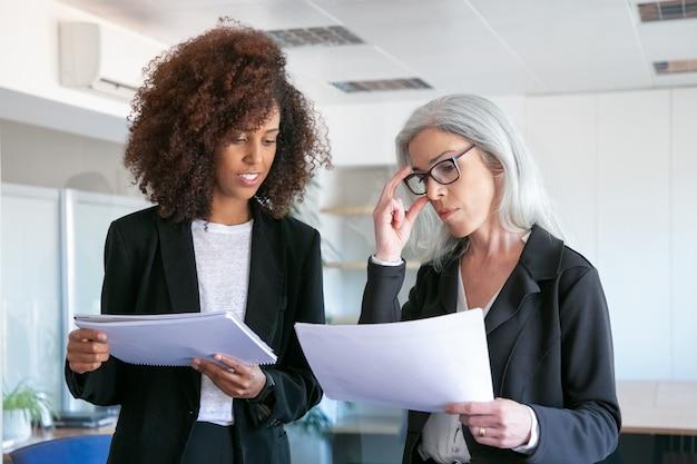 Content manager in brille lesedokument mit jungen kollegen. zwei erfolgreiche content-geschäftsfrauen, die statistikdaten studieren und sich im büroraum treffen. teamwork-, geschäfts- und managementkonzept Kostenlose Fotos