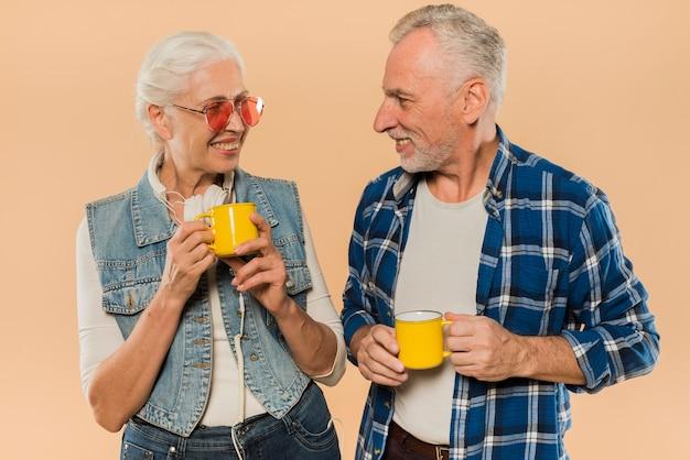 Coole ältere paare mit bechern Kostenlose Fotos