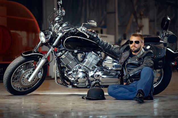 Cooler mann biker in sonnenbrille sitzt in der nähe seines motorrades Premium Fotos