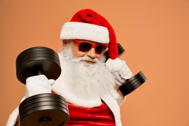 Cooler weihnachtsmann mit echtem barttraining mit zwei hanteln Premium Fotos