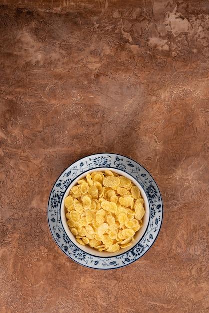 Cornflakes in einer platte auf einem braunen hintergrund. Premium Fotos