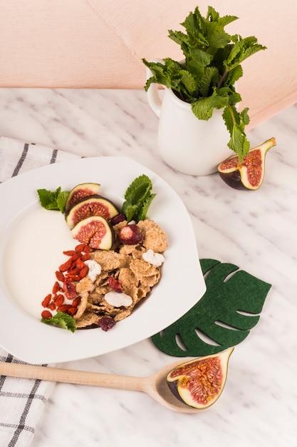 Cornflakes mit feigenfrucht und tadellosen blättern auf verzierter platte über marmorarbeitsplatte Kostenlose Fotos