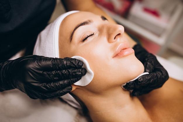 Cosmetologistreinigungsgesicht einer frau in einem schönheitssalon Kostenlose Fotos