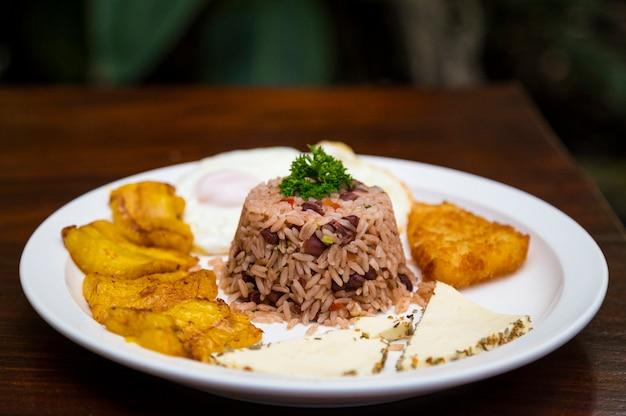 Costaricanische traditionelle mahlzeit in der weißen platte auf holztisch Kostenlose Fotos