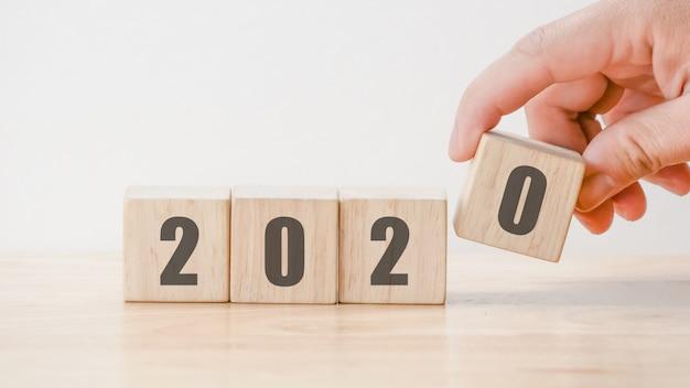 Count-down-konzept des entwurfes des neuen jahres 2020, hand, die würfel der hölzernen blöcke auf holztischhintergrund hält Premium Fotos