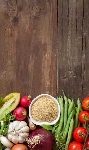 Cous cous in einer schüssel und frisches gemüse auf holz Premium Fotos