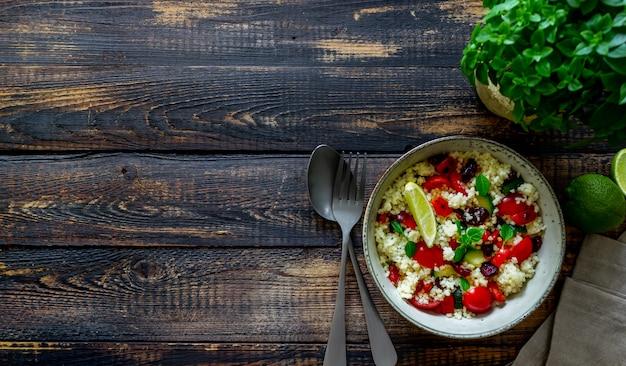 Couscous-salat mit tomaten, paprika, zucchini und preiselbeeren. vegetarisches essen. diät. gesundes essen. Premium Fotos