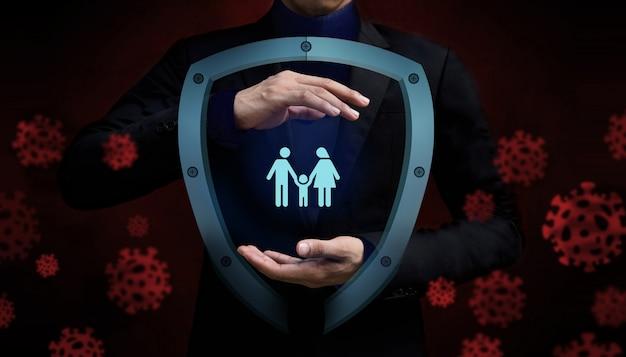 Covid-19- oder corona-virus-situationskonzept. versicherung für die familie. geschützt durch gestenhand und sicherheitsschildschutz Premium Fotos