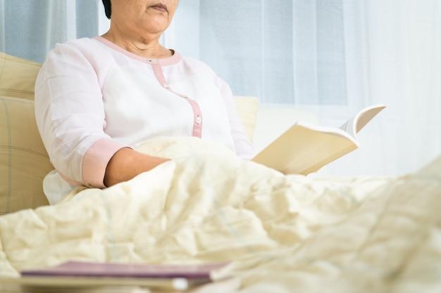 Covid-19-quarantäneaktivität für ältere frauen lesen ein buch zu hause bleiben, um risiken zu vermeiden Premium Fotos