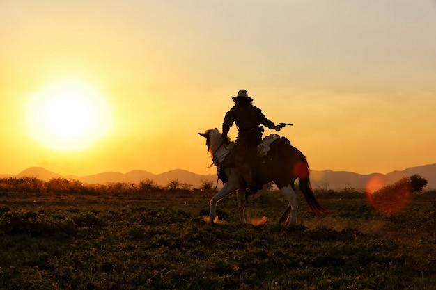 Cowboyreitpferde auf dem gebiet gegen sonnenuntergang Premium Fotos