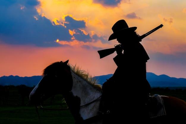 Cowboyschattenbild auf einem pferd während des netten sonnenuntergangs Premium Fotos