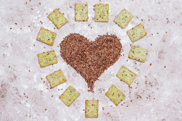 Cracker in form des herzens von den leinensamen mit olivenöl, leinensamen und grüns, draufsicht Kostenlose Fotos