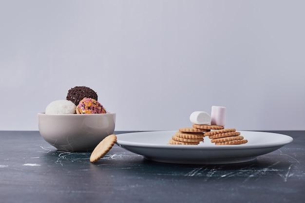 Cracker mit marshmallow-keksen in weißen schalen auf blau. Kostenlose Fotos
