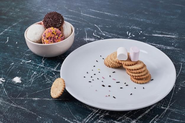 Cracker mit marshmallow-keksen in weißen schalen, draufsicht. Kostenlose Fotos