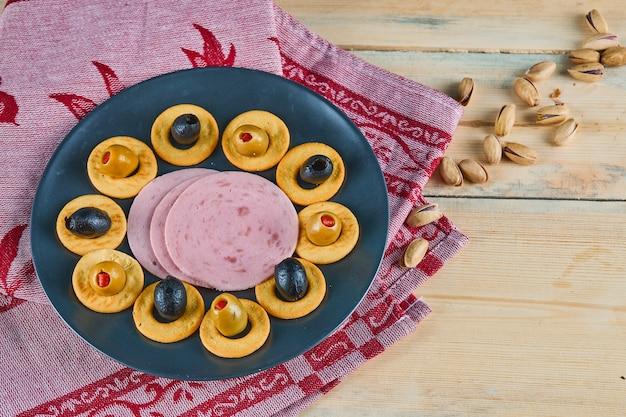 Cracker-ringe und würstchen mit oliven auf einem keramikteller mit rosa tischdecke. Kostenlose Fotos