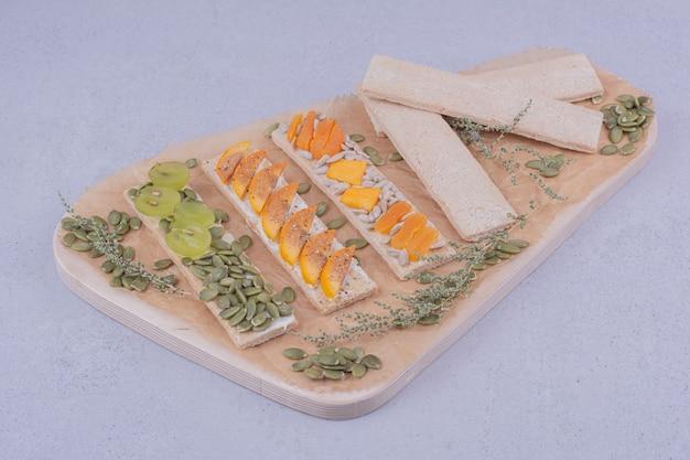Crackersandwiches mit kräutern und früchten auf einem holzbrett Kostenlose Fotos