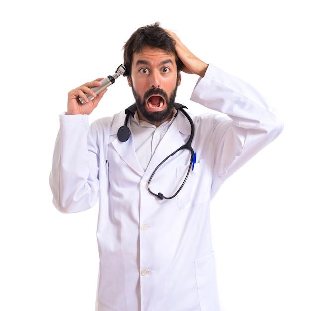 Crazy otorhinolaryngologist mit seinem otoscope über weißem hintergrund Kostenlose Fotos