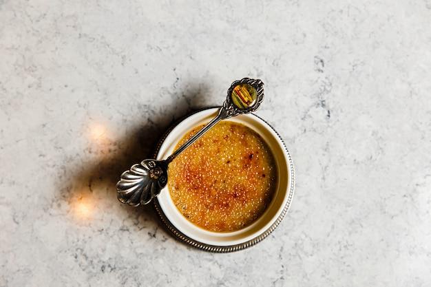 Creme brulee dessert mit einem schönen alten löffel auf einem marmortisch, draufsicht Premium Fotos