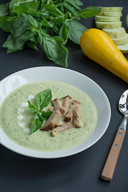 Cremesuppe aus kartoffelpüree mit zucchini und basilikum und crackern Premium Fotos