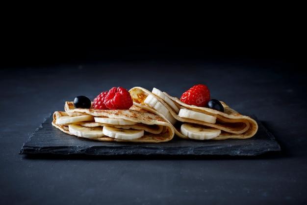 Crêpe mit banane, erdbeere und schokolade Premium Fotos