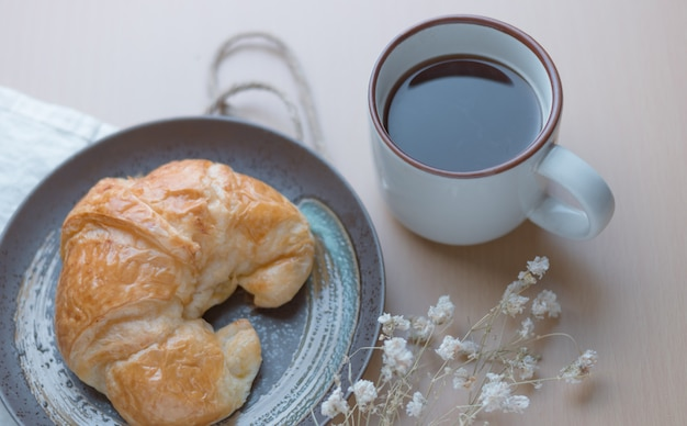 Croissant mit einer tasse schwarzen kaffee Premium Fotos