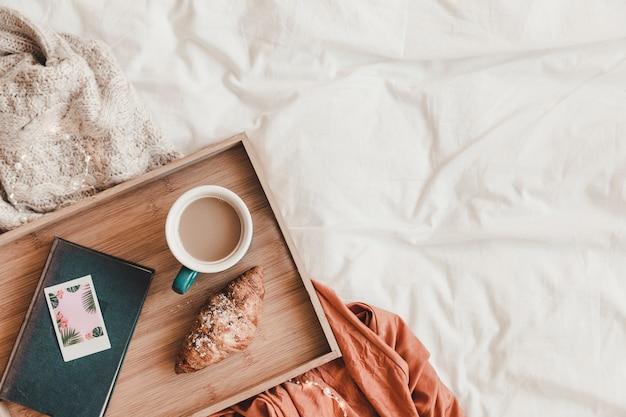 Croissant und kaffee in der nähe von buch auf dem bett Kostenlose Fotos