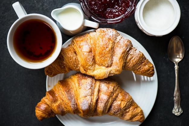 Croissants mit zuckerguss, tasse tee, milch, zucker und erdbeermarmelade Premium Fotos
