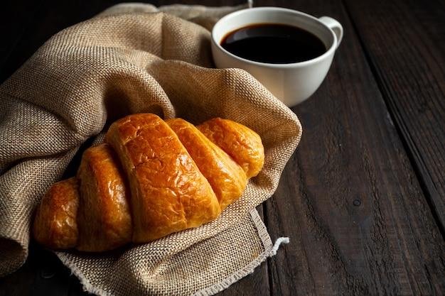 Croissants und kaffee auf alten holztisch. Kostenlose Fotos