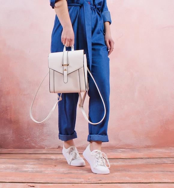 Crop foto einer frau, die einen modischen lederrucksack in ihrer hand gegen den tisch einer lehmwand hält. modekonzept Premium Fotos