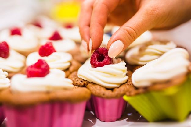 Crop hand dekorieren muffin mit himbeeren Kostenlose Fotos