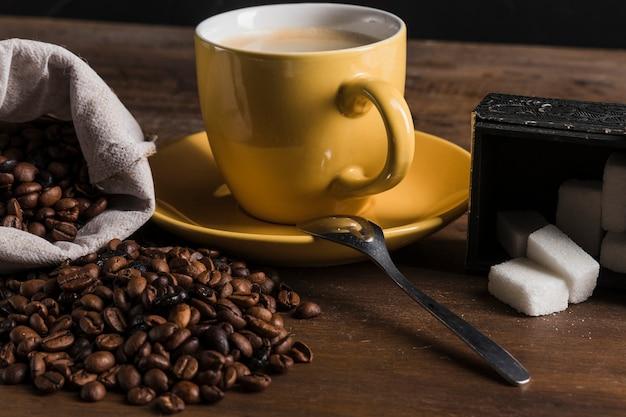 Cup nahe zuckerdose und sack mit kaffeebohnen Kostenlose Fotos
