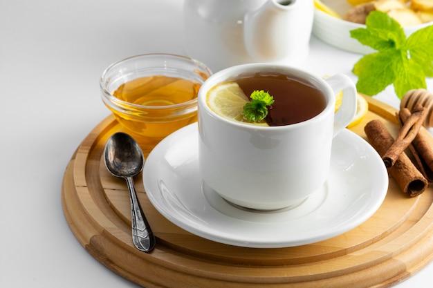 Cup tee mit zitrone und honig auf einem weiß. heiße teeschale lokalisiert, draufsicht. herbst-, herbst- oder wintergetränk. copyspace. Premium Fotos