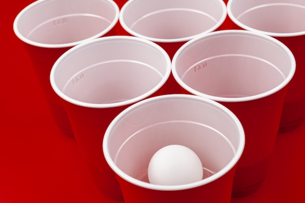 Cup und plastikkugel auf rotem hintergrund. bier-pong-spiel Premium Fotos