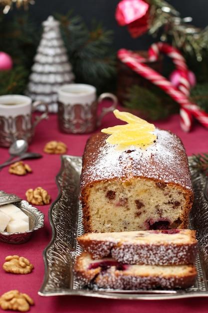 Cupcake mit beeren, nüssen und kandierten früchten befindet sich auf einer weihnachtsebene Premium Fotos