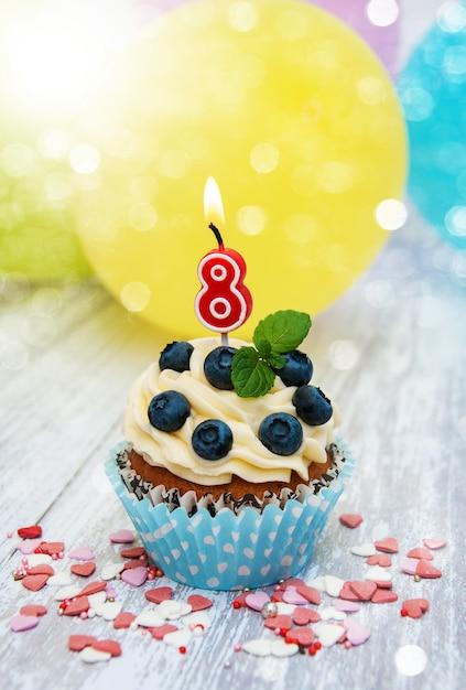 Cupcake mit einer kerze nummer acht Premium Fotos