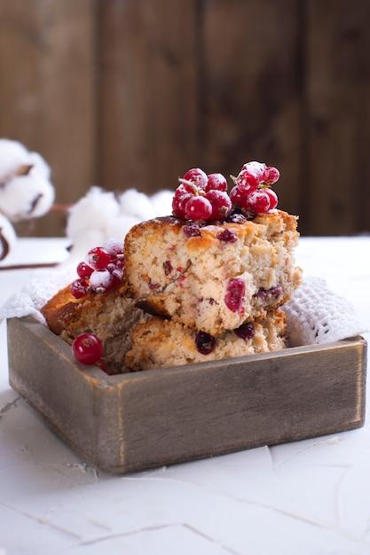 Cupcake mit roten johannisbeeren bestreut mit weißem zucker pulver, auf einem holzbrett und weißem hintergrund, baumwolle blumen Premium Fotos