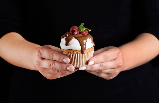 Cupcake mit weißer sahne, mit schokolade gewässert, mit himbeeren und minze in den händen eines konditoren geraspelt. Premium Fotos