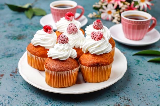 Cupcakes dekorierten schlagsahne und gefrorene himbeeren. Kostenlose Fotos