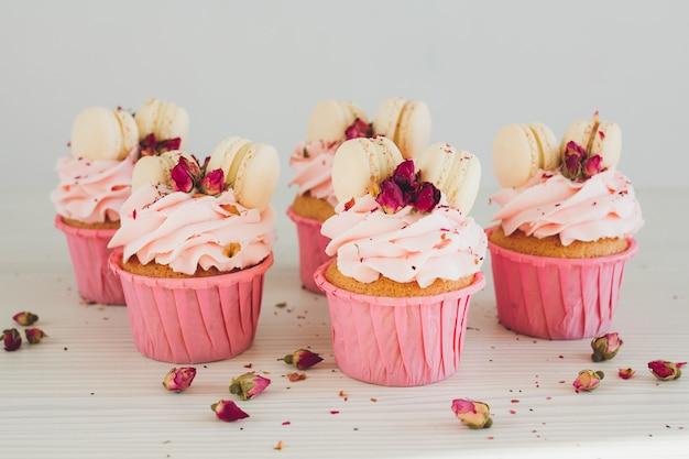 Cupcakes mit rosa sahne, makronen und rosen Premium Fotos