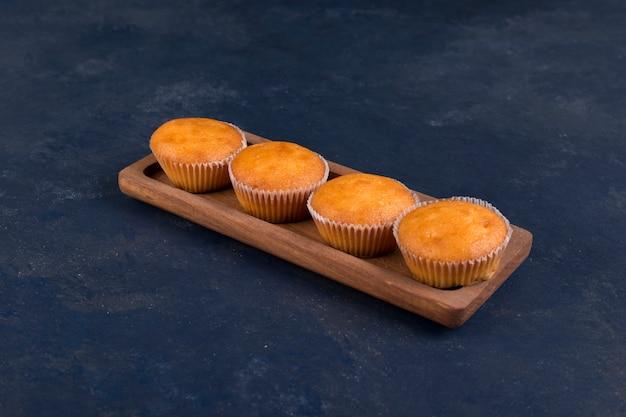 Cupcakes serviert in einer hölzernen schmalen platte, winkelansicht Kostenlose Fotos