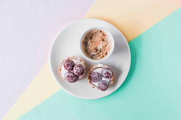 Cupcakes und kaffee auf tri farbigem hintergrund Kostenlose Fotos