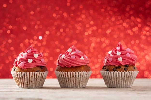 Cupcakes verziert mit zuckerherzen zum valentinstag auf holztisch und rotem hintergrund Premium Fotos