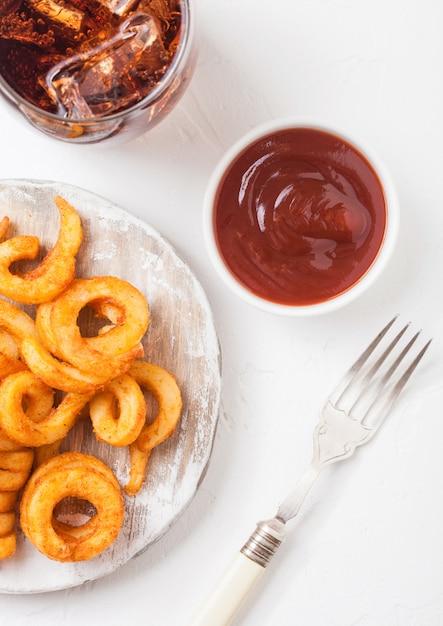 Curly pommes fast-food-snack auf holzbrett mit ketchup und glas cola auf küche. ungesundes junk food Premium Fotos