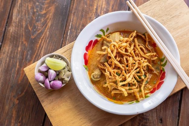Currynudelsuppe (khao soi) mit hühnerfleisch und würziger kokosmilch auf hölzerner tabelle. Premium Fotos