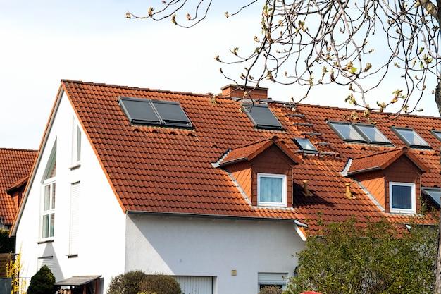 Dach von klassischen wohnhäusern mit orange dachziegeln und fenstern Premium Fotos