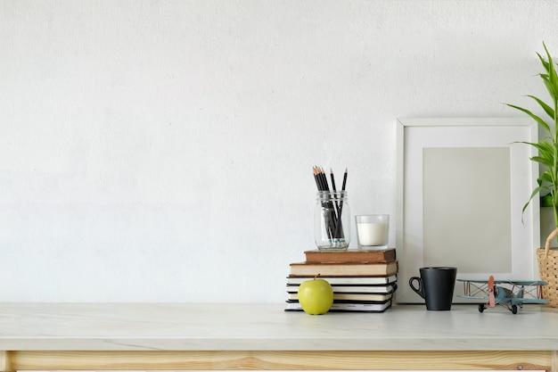 Dachbodenarbeitsplatz mit leerem plakat auf weißem hölzernem schreibtisch. Premium Fotos