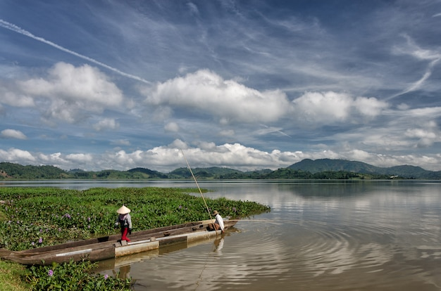 Dak lak-viet nam: eine gruppe asiatischer landwirte fährt im herbst mit dem ruderboot auf dem lak-see zur arbeit Premium Fotos